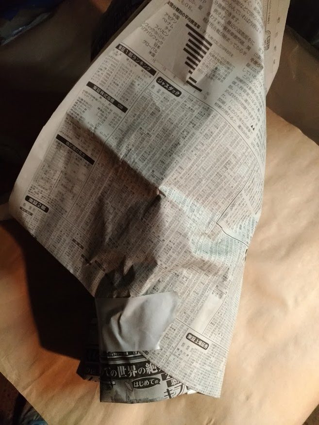シクラメンを上まですっぽり新聞紙でまく